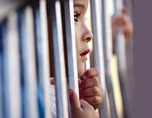 young child behind bars