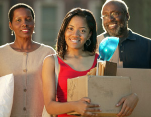 Parents with daughter on first day of college, carrying boxes