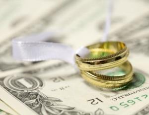 wedding rings sitting atop dollar bills