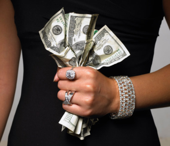 Woman gripping money with jewelry on