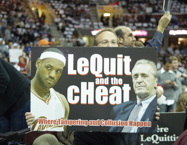 Angry Cavs fan holding poster of Lebron James and Pat Riley