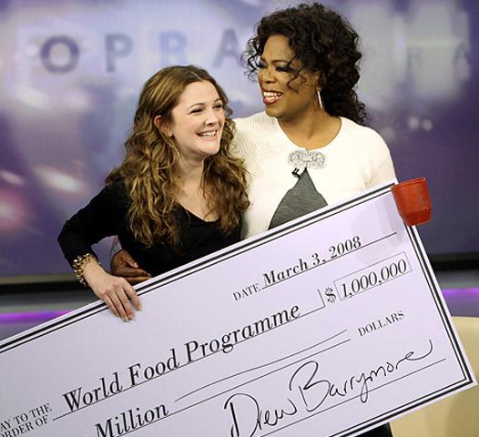 Oprah Winfrey recieving a $1 million dollar check from Drew Barrymore