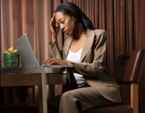Black woman exhausted and stressed at desk