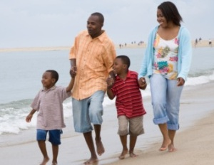 black family walking barefoot along the beach