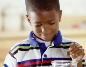 black kid putting money in piggy bank