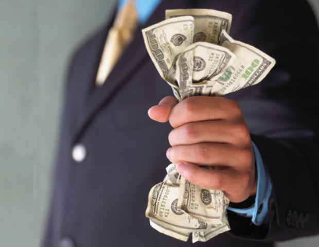 Black man in a suit with a fist full of money