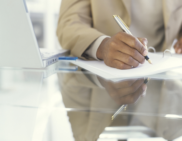 Businessman writing on document with fountain pen, close up