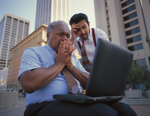Shocked businessmen looking at computer