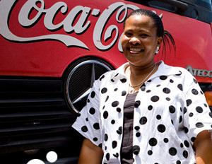 black woman in front of coca cola truck logo