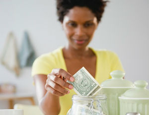 a black woman in a yellow t-shirt putting money away in a glass jar
