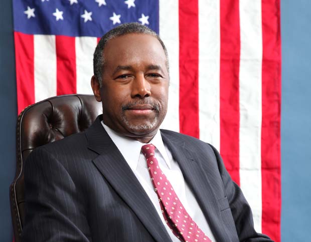 Ben Carson seated before American flag